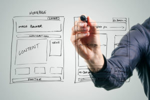 designer drawing website development wireframe with black marker